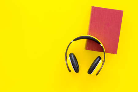 Distance education, e-learning concept. Headphones near hardback book with empty cover on yellow background top view copy space 版權商用圖片
