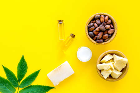 Cosmetics with cocoa butter for skin care. Cocoa beans and cocoa butter in bowl, soap, cream, oil or lotion in small bottles on yellow background top view copy space Stock Photo