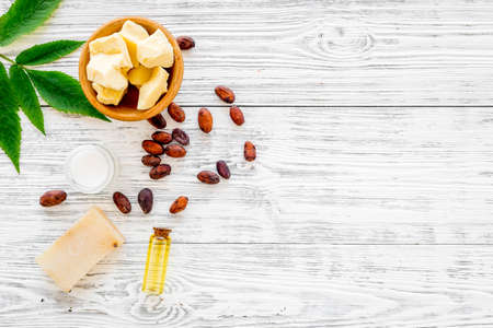 Natural organic cosmetics based on cocoa butter. Cocoa beans and cocoa butter, soap, cream, oil or lotion in small bottles on grey background top view copy space Stock Photo