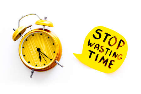 Stop wasting time hand lettering near alarm clock on white background top view. Business concept, motivation