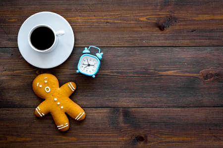 Hurry up concept. Gingerbread man near alarm clock on dark wooden background top view copy space