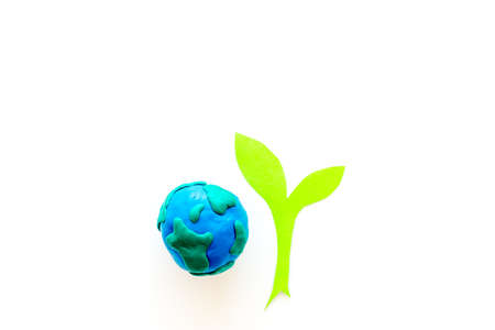 Planet, ecology. Plasticine symbol of planet Earth globe and plant cutout on white background top view copy space