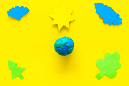 Environment protection concept. Plasticine symbol of planet Earth and sun, cloud, tree cutout on yellow background top view copy space