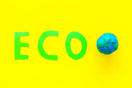 Eco icon cutout near planet Earth Plasticine symbol on yellow background top view copy space 스톡 콘텐츠