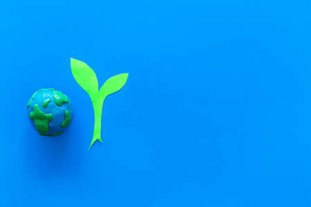 Planet, ecology. Plasticine symbol of planet Earth globe and plant cutout on blue background top view space for text Banco de Imagens