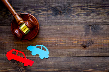 Car accident lawsuit concept. Two collided cars near judge gavel on dark wooden background top view copy space