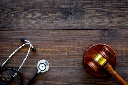 Droit médical, concept de droit de la santé. Marteau et stéthoscope sur fond en bois foncé vue de dessus copie espace Banque d'images
