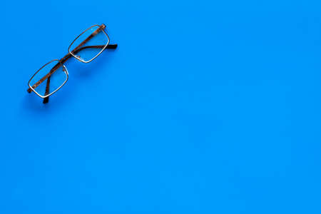 One glasses with transparent lenses on blue background top view copy space