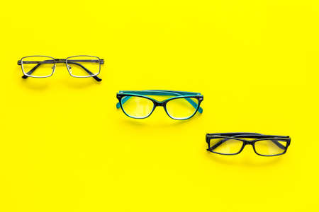 Glasses concept. Set of glasses with different eyeglass frame and transparent lenses on yellow background top view copy space pattern Stock Photo