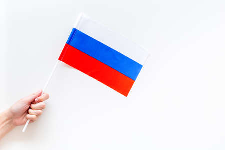Russian flag concept. Hand hold small flag on white background top view copy space
