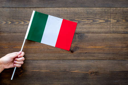 Italian flag concept. Hand hold small flag on dark wooden background top view copy space