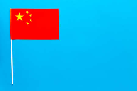 Chinese flag concept. small flag on blue background top view copy space 스톡 콘텐츠