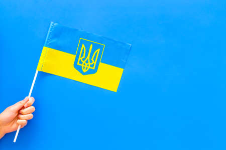 Ukrainian flag concept. Hand hold small flag on blue background top view copy space Reklamní fotografie