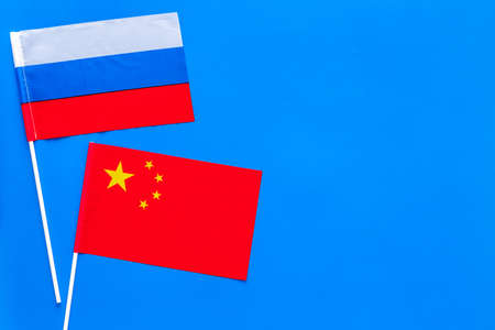 China-Russia relations. Country cooperation. Russian and Chinese flags on blue background top view copy space