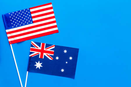 USA-Australia relations. Country cooperation. American and Australian flags on blue background top view copy space Reklamní fotografie - 104544668