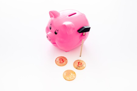 Savings. Moneybox in shape of pig near coins on white background copy space