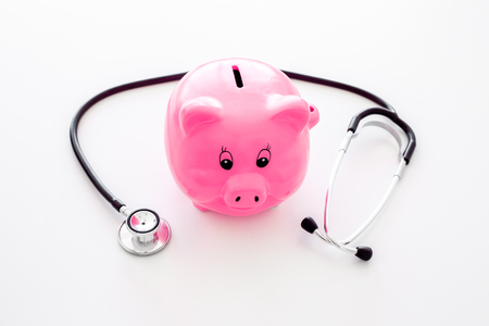Money for treatment. Medical expenses. Moneybox in shape of pig near stethoscope on white background Zdjęcie Seryjne
