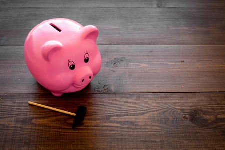Piggy bank. Moneybox in shape of pig near hammer on dark wooden background copy space Stock Photo