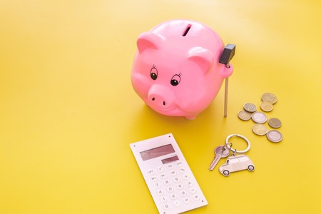 Money for buy car. Moneybox in shape of pig near keychain in shape of car, coins, calculator on yellow background copy space Stockfoto