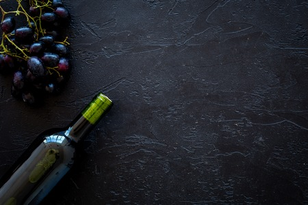 Red wine concept. Glass bottle with beverage near bunch of grapes on black background top view copy space Stockfoto