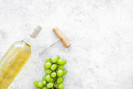 Open the wine concept. White wine in glass bottle near bunch of grapes and corkscrew on grey background top view copy space