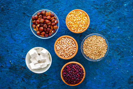 Products rich protein. Legumes, nuts, low-fat cheese. Raw beans, chickpeas, lentil, almond, hazelnut on blue background top view Stock Photo