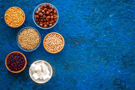 Products rich protein. Legumes, nuts, low-fat cheese. Raw beans, chickpeas, lentil, almond on blue background top view copy space