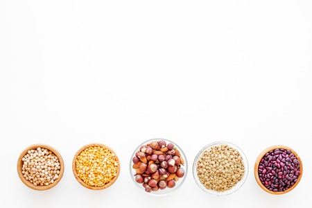 Vegan protein source. Legumes and nuts on white background top view. Stock Photo