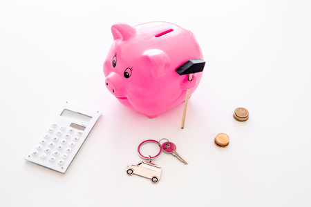 Money for buy car. Moneybox in shape of pig near keychain in shape of car, coins, calculator on white background. Stock Photo
