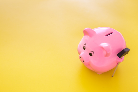Piggy bank. Moneybox in shape of pig near hammer on yellow background.