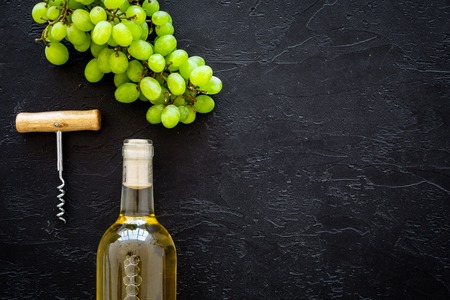 Open the wine concept. White wine in glass bottle near bunch of grapes and corkscrew on black background top view.