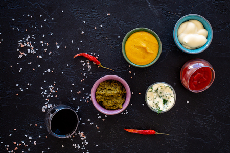 Set of sauces. Ketchup, mayonnaise, mustard, soy sauce, barbecue sauce, pesto, mustard, sour with greenery near chili pepper and salt on balack background top view copy space Reklamní fotografie