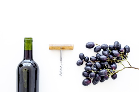 Red wine concept. Glass bottle with beverage near bunch of grapes and corkscrew on white background top view space for text Stock Photo