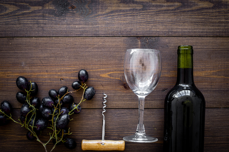 Composition with wine. Red wine bottle, bunch of grapes, corkscrew, wine glass on dark wooden background top view.
