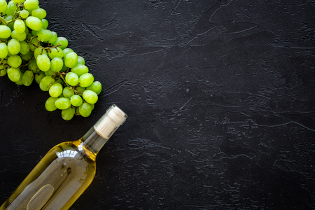 White wine in glass bottle near bunch of grapes on black background top view. Stockfoto
