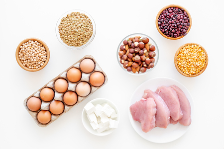 Healthy food. Products rich protein and fiber. Legumes, nuts, low-fat cheese, meet, eggs. Raw beans, chickpeas, lentil, almond, hazelnut on white background top view