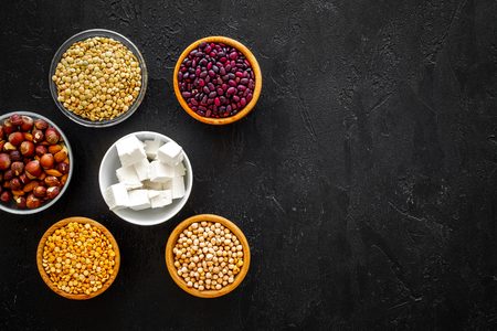 Products rich protein. Legumes, nuts, low-fat cheese. Raw beans, chickpeas, lentil, almond, hazelnut on black background top view copy space Stock Photo