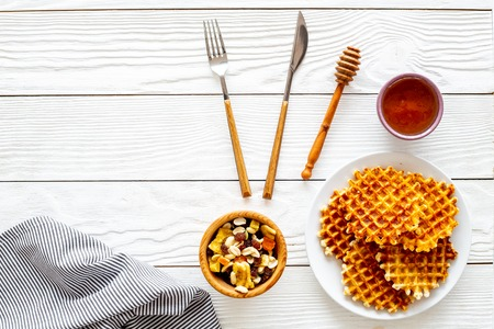 Traditional belgian waffles near dried fruit, nuts and honey on served table with tablecloth on white wooden background top view copy space