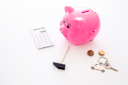 Money for buy car. Moneybox in shape of pig near keychain in shape of car, coins, calculator on white background. Stockfoto