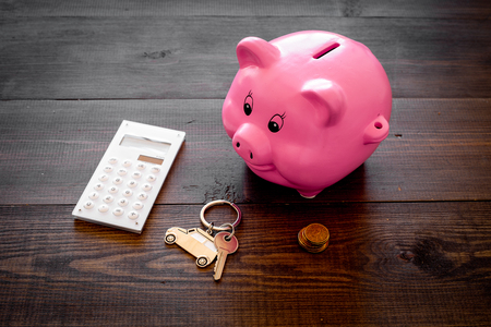 Money for buy car. Moneybox in shape of pig near keychain in shape of car, coins, calculator on dark wooden background.
