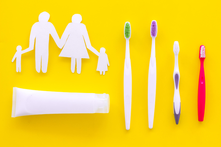 Teeth care, dental care. Toothbrushes and tooth paste near family silhouette on yellow background top view. Stock Photo - 106319976