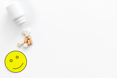 Reception of medicines concept. Recovery. Pills falling out of jar near smile face emoji on white background top view. Stock Photo
