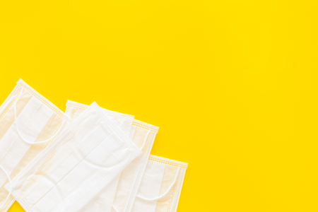 Flu prevention. Medical face masks on yellow background top view.