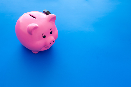 Piggy bank. Moneybox in shape of pig near hammer on blue background. Stock Photo