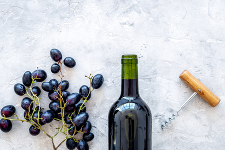 Red wine concept. Glass bottle with beverage near bunch of grapes and corkscrew on grey background top view.