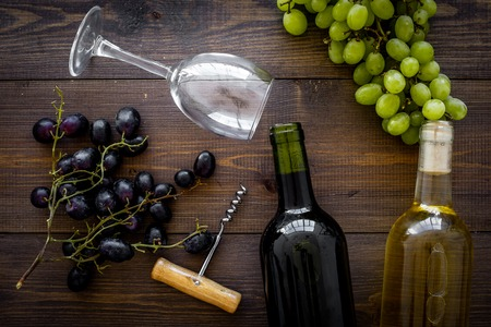 Composition with wine bottles. Red and white wine bottles, bunch of grapes, corkscrew, wine glasses on dark wooden background top view. Stockfoto
