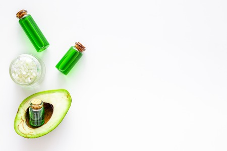 Cosmetics for skin care. Avocado oil near half of avocado on white background top view copy space 스톡 콘텐츠