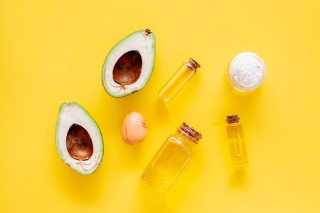 Cosmetics for skin care. Avocado oil near half of avocado on yellow background top view copy space 스톡 콘텐츠