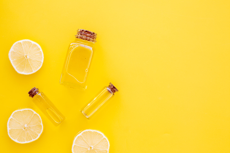 Natural cosmetics. Lemon essential oil near halfs os lemons on yellow background top view.