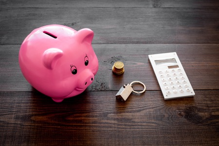 Mortgage. Savings for buy house. Moneybox in shape of pig near keychain in shape of car, coins, calculator on dark wooden background. Stockfoto